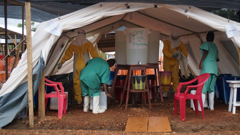Health workers carry out disinfection protocols at a MSF Ebola Treatment Center in Kailahun, Sierra Leone. (photo cc-by-sa European Commission DG-ECHO)