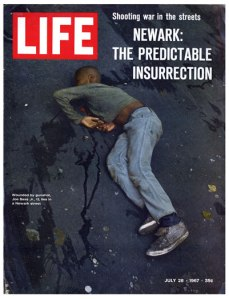 Joe Bass, Jr. lies wounded by the National Guard during the 1967 uprising in Newark. The shot which ricocheted and injured him killed William Furr, who was fleeing Guardsmen after stealing a six-pack of beer.