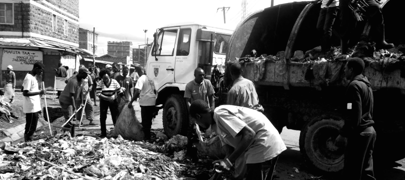Men and women rake and shovel a plie of garbage into bags as part of the Kariobangi Waste Management Allianc