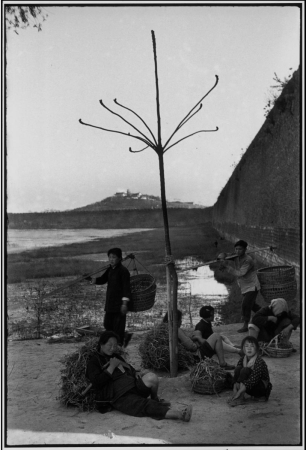 Peasants rest at the foot of the ancient walls of Nanking after collecting lotus roots for fuel. In the background: Jade Mountain, and the lake where sailors received their training during the days of the Ming Emperors.